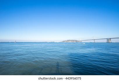 landmark bay bridge over tranquil sea in blue sky