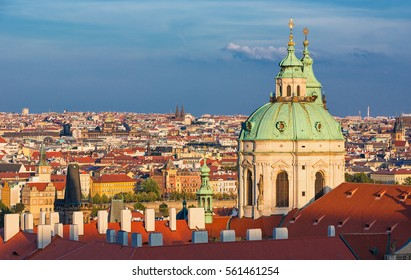 Landmark St Nicholas Catholic Church stands tall above typical red roofs and church spires of Mala Strana,Prague,Czech Republic