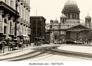 Landmark in St Petersburg, Russia: Saint Isaac's Cathedral and square in front of it by winter day with streets and trees, old buildings, cars and people.  Black and white retro photo.