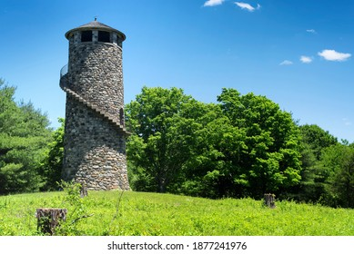 The landmark stone tower at camp columbia state park and forest in Morris connecticut on a sunny summer new england day.