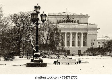 Landmark and touristic spot in St Petersburg, Russia: historical Alexandrinsky theater and square in front of it by a winter day with snow and old vintage lantern.  Black and white retro photo.