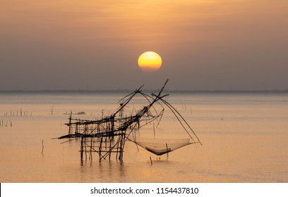 Landmark of traditional fishing net tools in the lake with beautiful morning sunrise at Pakpra village, Phatthalung Province, Thailand.