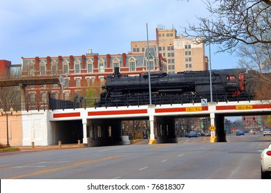 """Landmark train is parked over downtown overpass in Wichita, Kansas.  Train is part of """"Old Town"""" attractions.  Eaton Hotel is seen in background as is traffic lights and traffic."""