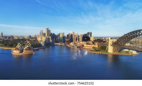 Landmarks of Sydney city CBD on Harbour waterfront around Circular Quay with arch of the Sydney Harbour bridge in warm light of morning sun under blue sky.