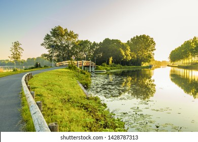 Landscape Aarkanaal with cycle path and bridge in Alphen aan den Rijn with water vapor in warm light sunrise with sides of trees lined with poplar shores covered with reeds and moored boats