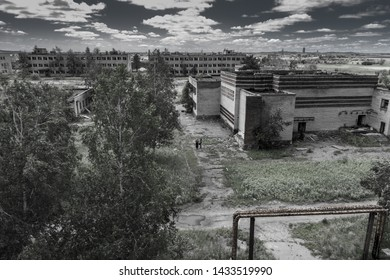 Landscape of abandoned city ghost town, with modern, but rusty and ruined empty houses, barracks, and two lonely little figures of rambler adventurers inside. Post apocalypse world