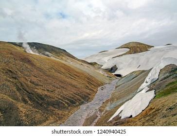 Landscape of active geothermal area Jokultungur with steaming ground and rhyolite mountains under snow, Laugavegur trail (Laugavegurinn), near Landmannalaugar, Fjallabak Nature Reserve, Iceland