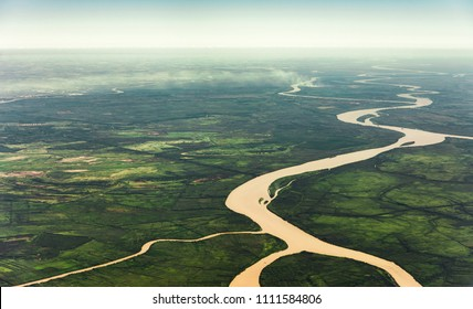 Landscape aerial view of colorful Amazon rivers, forest with trees, jungle, and fields - Shutterstock ID 1111584806