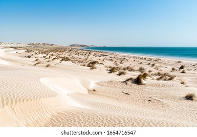 Landscape of Al Khaluf beach with dunes and white sands in the Arabian Sea of Oman in the Middle East.
