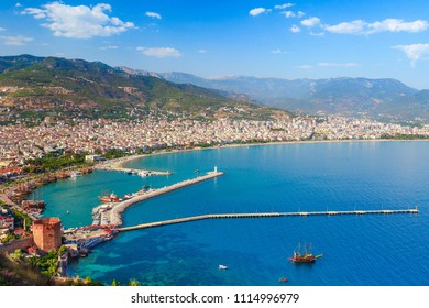 Landscape of Alanya with marina and Kizil Kule red tower in Antalya district, Turkey, Asia. Famous tourist destination with high mountains. Summer bright day and sea shore