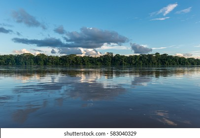 Landscape of the Amazon river with a beautiful cloud reflection. The tributaries of the river flow through the countries of Guyana, Venezuela, Colombia, Ecuador, Peru, Bolivia and Brazil.