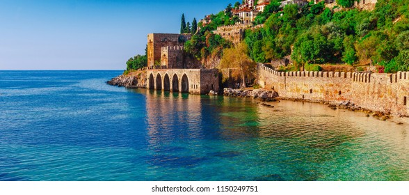 Landscape of ancient shipyard near of Kizil Kule tower in Alanya peninsula, Antalya district, Turkey, Asia. Famous tourist destination with high mountains. Part of ancient old Castle.