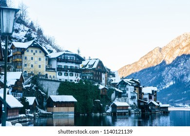 Landscape around the Hallstatt Town. Panoramic Beautiful view of traditional wooden houses in famous Hallstatt lakeside town in Alps on beautiful day in winter with snow, Salzkammergut region, Austria