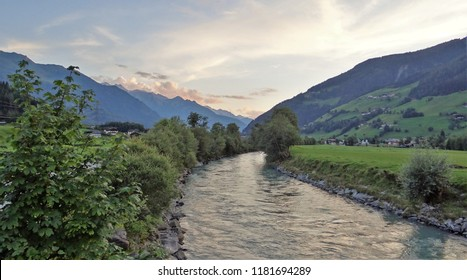 A landscape in Austria in the Pinzgau near by Bramberg with the river the Salzach and beautiful mountains of the Alps at the background on a summer evening