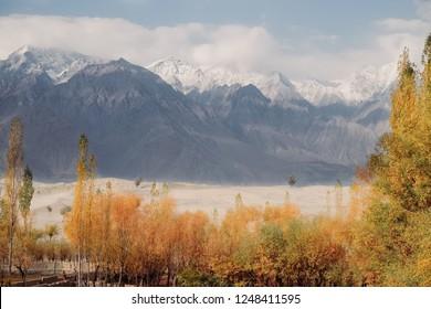 Landscape autumn scene of snow capped mountains and Katpana desert in Skardu. Gilgit Baltistan, Pakistan.