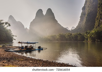 Landscape with bamboo boat on Li river and mountains in the background.