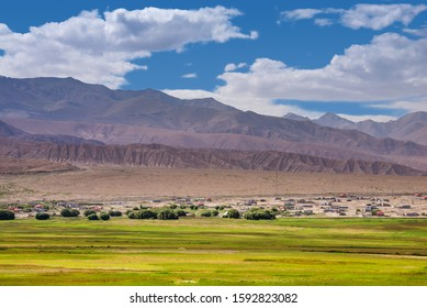 Landscape of barren mountain ranges,desert,pasture,village and cloudscape in Pamirs plateau in Xinjiang of China