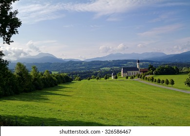 Landscape in Bavaria, Germany, church with mountains in the background