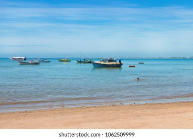 Landscape Beach of Rio das Ostras with fishing boats and man swimming and stand up paddle