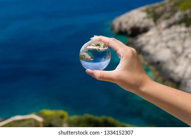 Landscape of a beautiful blue and green sea shore in background, young girl's hand with glass sphere, outdoor.