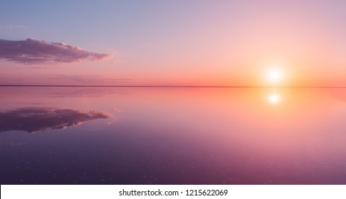 Landscape beautiful golden sunset red sky solt lake saline Elton Baskunchak. The sun sets behind the horizon