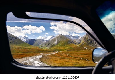 Landscape of beautiful mountain valley viewed from the car window. Travel and adventure concept.