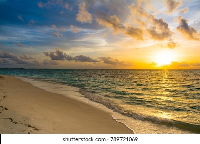 Landscape of beautiful sunset in Maldives island sandy beach with colorful sky and dramatic  clouds over wavy sea