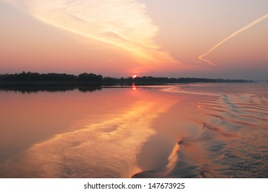 the landscape is beautiful sunset on the river, and traces of the boat on the water