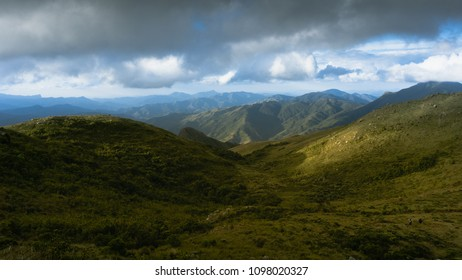 Landscape of beautiful valley of green mountains with a shine light of the sunset and heavy cloud at the blue sky
