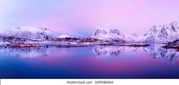 Landscape with beautiful winter lake and snowy mountains at sunset at Lofoten Islands in Northern Norway. Panoramic view
