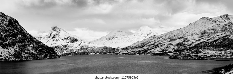 Landscape with beautiful winter lake and snowy mountains at Lofoten Islands in Northern Norway. Panoramic view, black and white