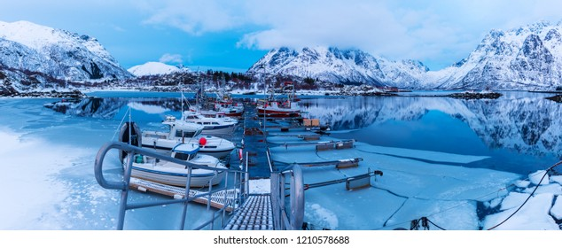 Landscape with beautiful winter lake, snowy mountains and pier with fishing boats at Lofoten Islands in Northern Norway. Panoramic view