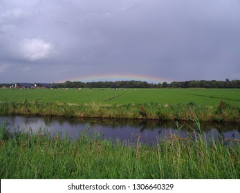 Landscape with beuatyfull rainbow and real dutch cloads with an ditch and green grass