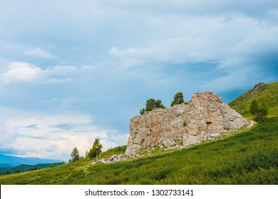 Landscape with big rocky stone on hill in highland under cloudy sky. Rock on mountainside with coniferous trees and rich vegetation. Wonderful scenic mountainscape. Amazing mountain scenery.