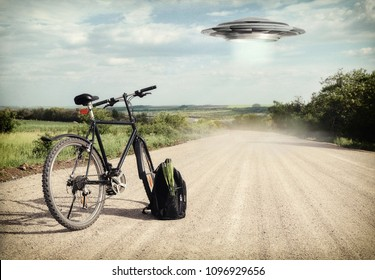 Landscape with bike on the road and UFO. Fiction scene with alien spaceship. Photo with 3d rendering element and vintage film camera effects