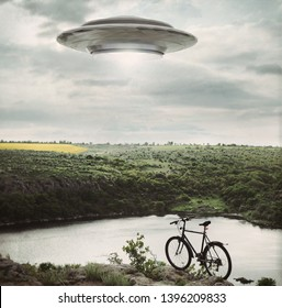 Landscape with bike standing on the edge of cliff and UFO. Fiction scene with alien spaceship. Photo with 3d rendering element and vintage film camera effects