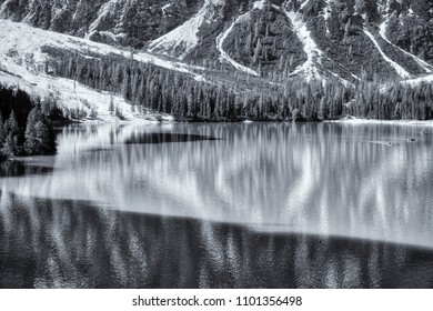 landscape in black and white of Braies lake in summer season with sunny light, shadow and mountain Croda del Becco in background, Dolomites - Italy