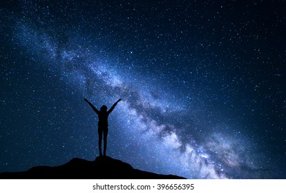 Landscape with blue Milky Way. Night sky with stars and silhouette of a standing sporty girl with raised-up arms on the hill