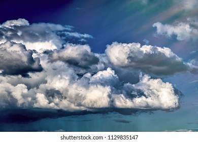 landscape in the blue sky with big white and gray clouds