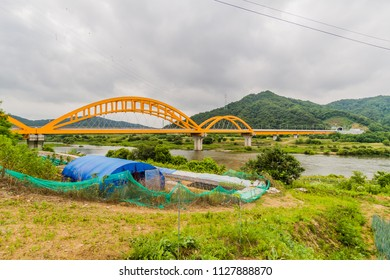 Landscape of blue tent structure surrounded by green mesh fence next to river with yellow arched railroad bridge spanning a river in background.