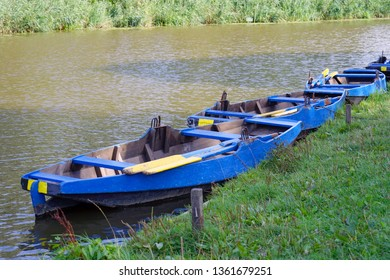 Landscape with blue wooden boats on the river. A row of boats by the river in the morning. Blue wooden boats with oars on the river. Netherlands. Europe.
