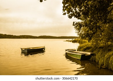 Landscape with boats for fishing on the lake at the shore. Vintage photo. Tranquil landscape stylized on vintage. Nature background.