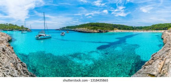 Landscape with boats and turquoise sea water on Cala Mondrago, Majorca island, Spain