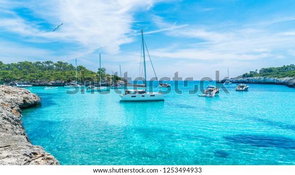 Landschaft mit Booten und türkisfarbenem Meerwasser auf Cala Mondrago, Mallorca, Spanien