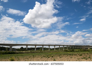 Landscape with a bridge and beautiful clouds over the blue sky.