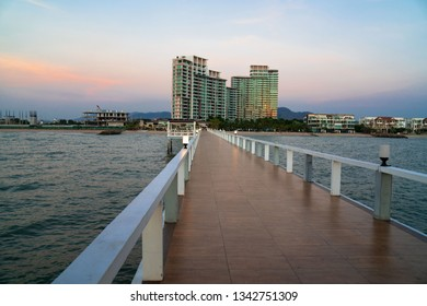 Landscape of bridge in sea on tropical beach and building and sunset sky background .