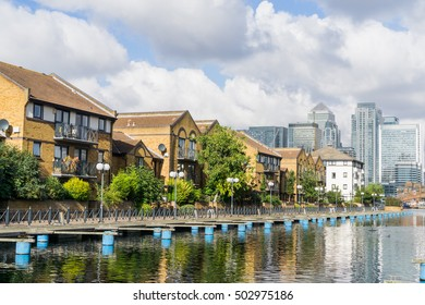 Landscape of British houses by the river canal, with skyscrapers in the background