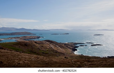 Landscape of the Caherdaniel Village area of the Ring of Kerry, Ireland. Blue ocean water, brown hills, blue sky with scattered clouds