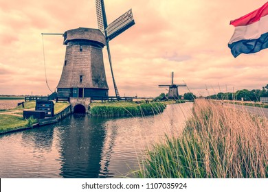 landscape with canal two windmills and dutch flag flying. Oterleek netherlands holland