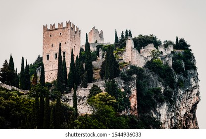 Landscape and Castello di Arco on rock at Garda lake of Trentino in Italy in evening. Scenery with ruins of castle on hill in Trento near Riva del Garda. Remains of tower in mountains at dawn.
